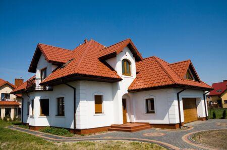 Single family small white house against blue sky