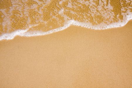 Wave of water on clear sandy beach Stock Photo