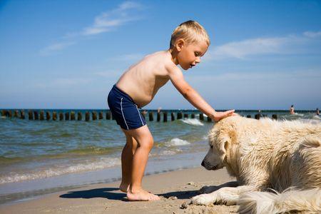 Small boy plays with a dog on a beach photo
