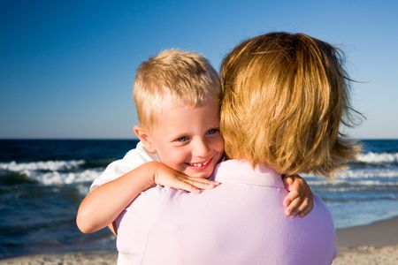 3 years old boy hugging his mother on a beach in sunny day Stock Photo - 5172030