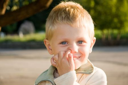 Three years old boy picking his nose outdoors Stock Photo - 5191601