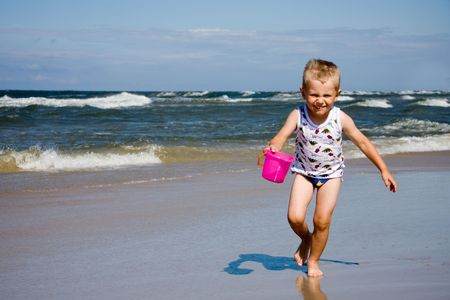 4 years old boy running on beach with bucket photo