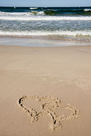 Two hearts drawn on a sandy beach in summer day photo