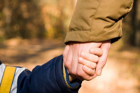 La madre tiene una mano de su hijo en el otoño de paisaje Foto de archivo - 5530197