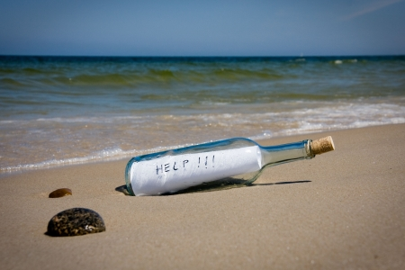 castaway: Help message in the bottle on a sea shore