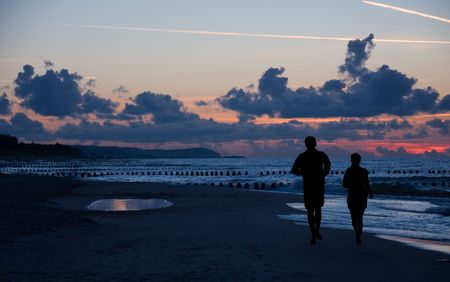 Silhouette of a couple running on a beach at suset photo