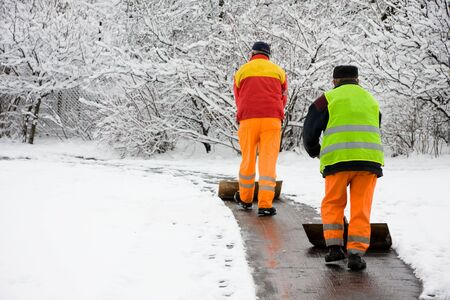 Workers removing first snow from pavement photo