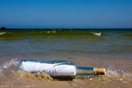 Help message in bottle in a sea shore photo