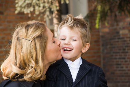blonde mom: Mother kissing her 4 years old son outdoors