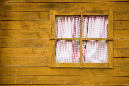 Window on yellow wooden wall made of planks