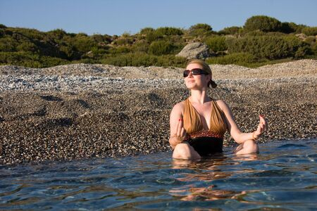 Woman doing yoga exercise in hot sea shore Stock Photo - 6632294