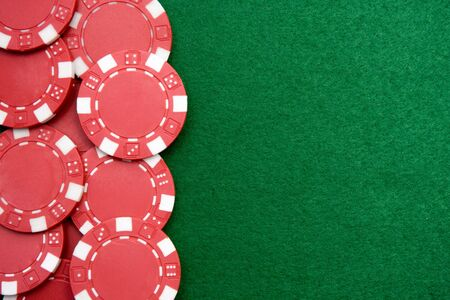 Red gambling chips on green felt background with copy space photo