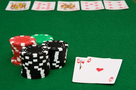 Royal flush of hearts on poker table and gambling chips on green felt photo
