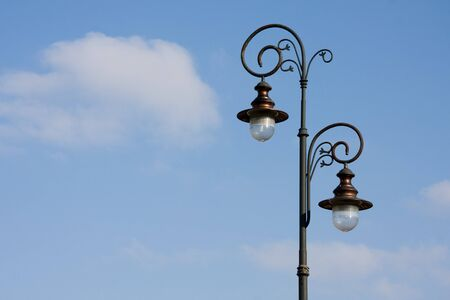 Antique lamppost on blue sky with some clouds and copy space photo