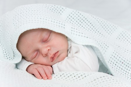 Newborn boy covered by blue blanket sleeping Stock Photo - 7072802