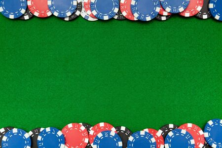 Colorful gambling chips on green felt background with copy space photo