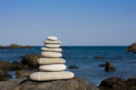 Eight white pebbles stacked on a beach photo