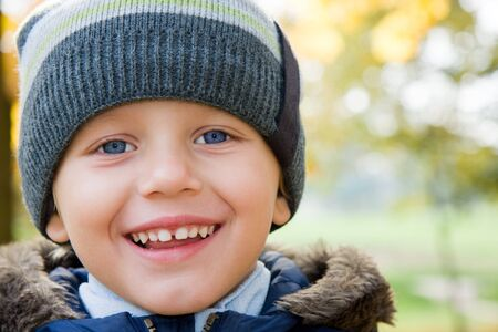 Three years old boy in cap smiling in autumn scenery Stock Photo