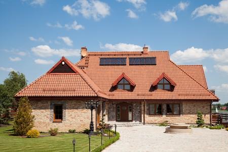 Einfamilienhaus aus Backstein mit roten Dach über blauer Himmel