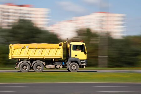 panning: Panning image of yellow truck in intentional motion blur Stock Photo