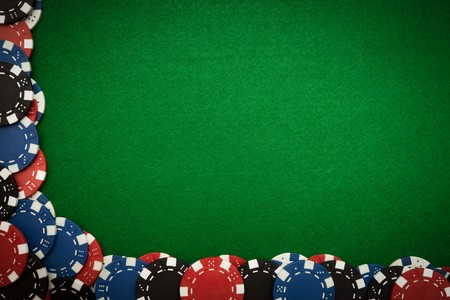 Colorful gambling chips on green felt background with copy space Stock Photo