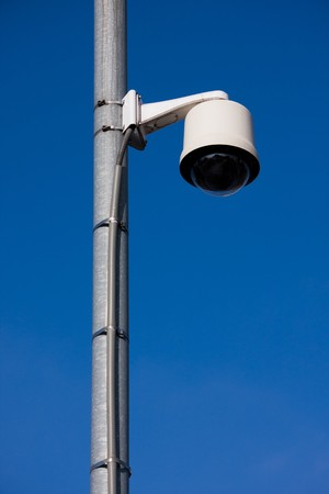 Security camera located on a post over a street photo