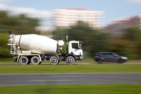 Panning image of cement mixer truck in intentional blurred motion on a street photo