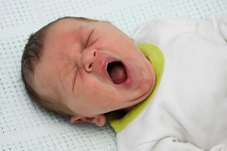 Newborn baby boy in yellow blanket yawning after bath photo
