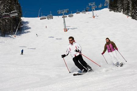 Man en vrouw bergafwaarts skiën op brede piste in bergen van de Alpen