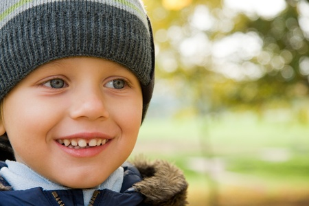 Three years old boy in cap smiling in autumn scenery photo
