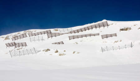 avalanche: Avalanche barriers protecting ski slopes in alps mountains Stock Photo