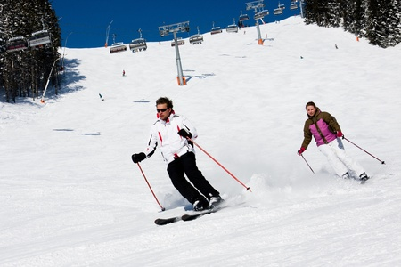 Man and woman downhill skiing on wide piste in alps mountains photo