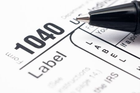 Filling in tax form 1040 by ballpen photo