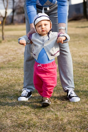 Mother helping son learn to walk outdoors photo