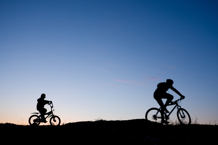 Silhouette of two bikers against sunset - father and son Stock Photo
