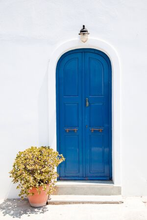 architectural styles: Traditional greek blue doors in white building Stock Photo
