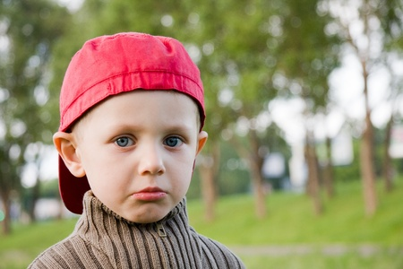 Sad small boy in red cap outdoors  photo