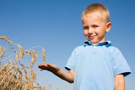 Boy pointing wheat ear in summer day on farm photo