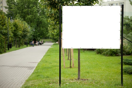outdoor advertising: Blank billboard on green grass in park
