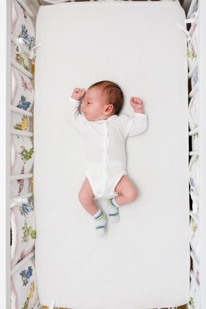 Newborn small boy lying in his big bed photo