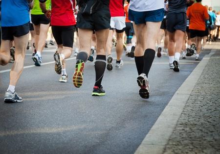 People running in city marathon on a street