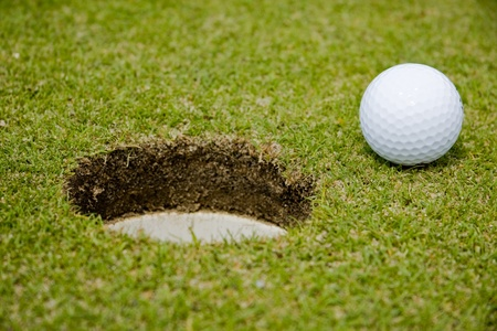 Golf ball very close to a hole on a putting green.  photo