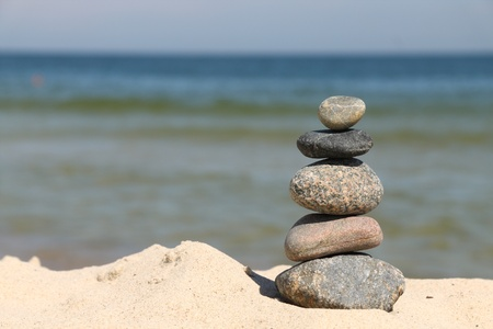 Five differently sized and colored pebbles, stacked over a sea photo