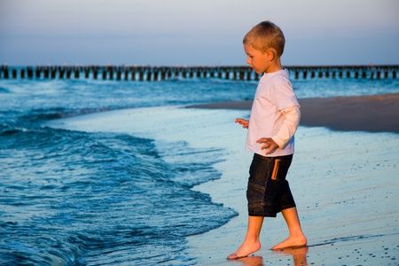 Boy going to sea water in sunset light photo