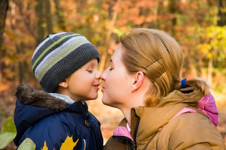 mom kiss son: Mother kissing her 3 years old son in autumn scenery