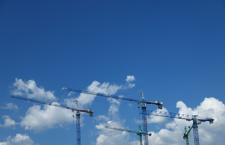 commercial activity: Construction cranes on site over blue sky