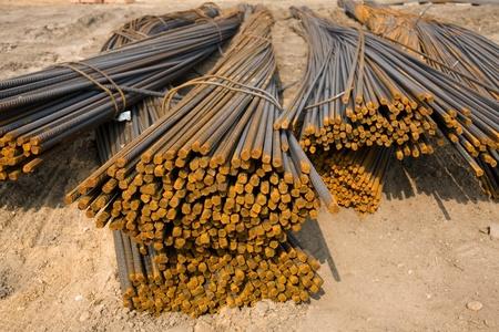 materia prima: Un montón de barras de metal oxidado en el sitio de construcción