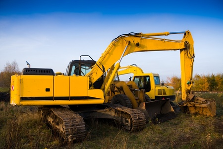 ble: Dirty yellow excavator and bulldozer over ble sky Stock Photo