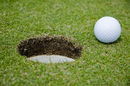 golfball: Golf ball close to a hole on putting green