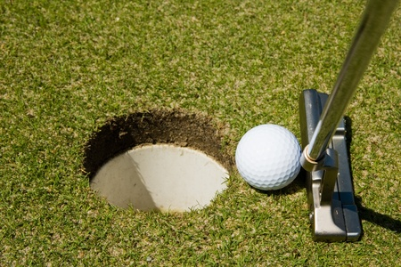 putting in: Putting golf ball to a hole Stock Photo